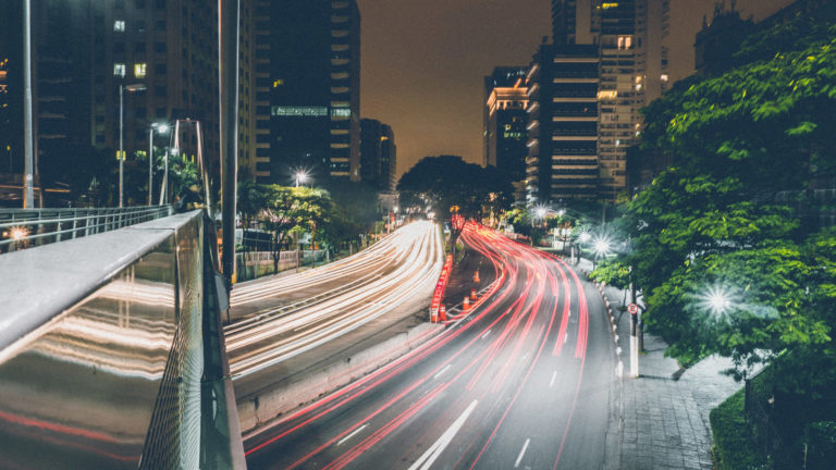 a city at night with car tail lights streaking down streets